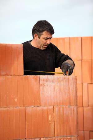 lagging: Mason checking that wall is straight