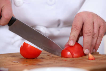 chopping: cook slicing tomato on a chopping board