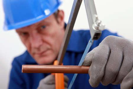 Plumber cutting copper pipe photo
