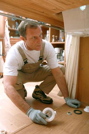 calzado de seguridad: fontanero debajo de un fregadero