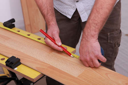 treated board: carpenter taking measurements to lay parquet Stock Photo