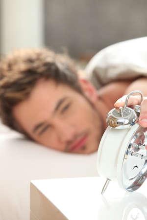 Man looking at his alarm clock Stock Photo - 22080506