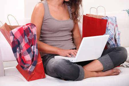 permanence: Woman sitting on sofa with computer and bags