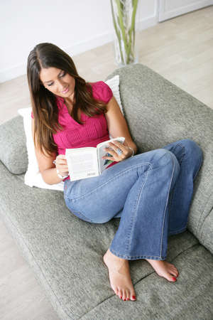 Woman enjoying a book on a sofa photo
