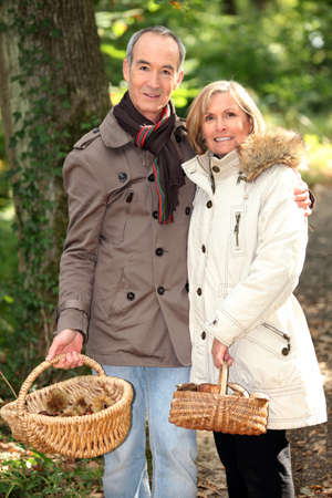 Middle-aged couple with basket of mushrooms photo