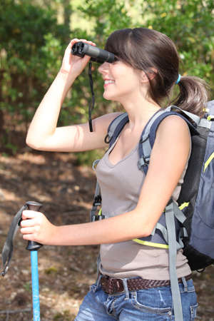 dignified: young woman backpacking and watching landscapes with binoculars