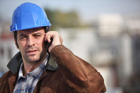 A construction foreman talking on his mobile phone