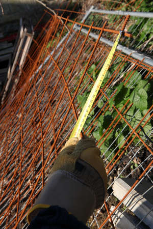 rusty wire: Worker measuring old rusty wire mesh Stock Photo