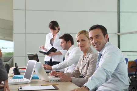 personas trabajando en oficina: Los colegas que trabajan en las computadoras portátiles en un entorno de oficina