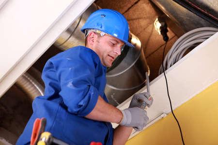 duct: Hombres examinar el sistema de ventilaci�n Foto de archivo