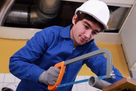 sawing: Young man sawing tube