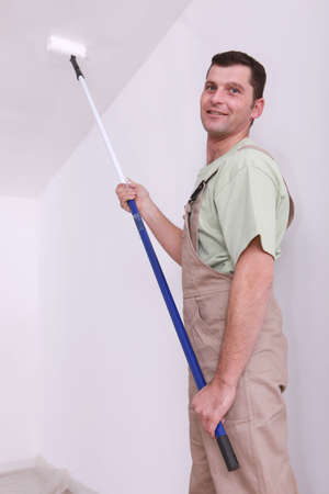 Decorator painting the ceiling photo