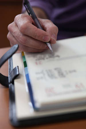 event organizer: Closeup of a male hand writing in a personal organizer Stock Photo