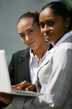 two businesswomen checking informations photo