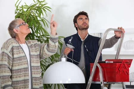 Handyman fitting a ceiling light