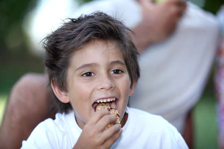 cereal bar: Little boy eating cereal bar outdoors Stock Photo