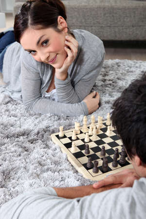 Couple playing chess on the floor photo