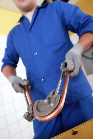gripping bars: Tradesman bending a copper tube Stock Photo