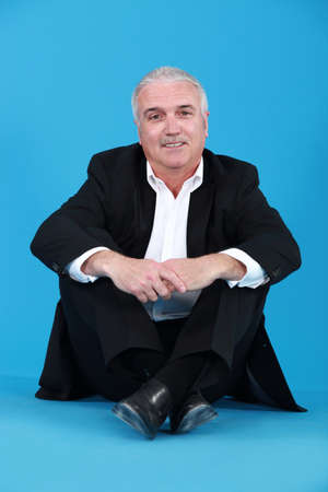 Senior businessman sitting on the floor photo