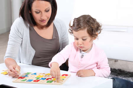 Mother and daughter completing a letter puzzle photo