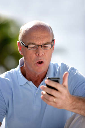disbelief: Man staring at his mobile phone is disbelief