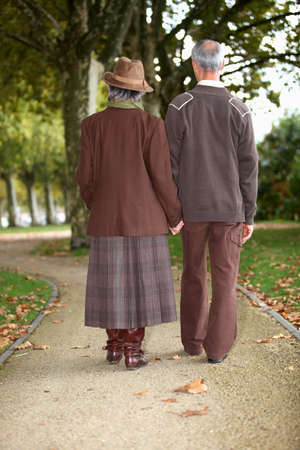Mature couple walking hand in hand photo