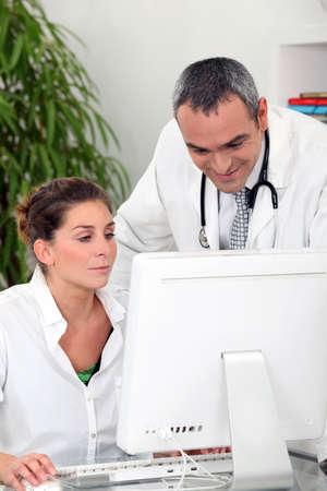 secretaria: médico y una secretaria médica mirando un ordenador