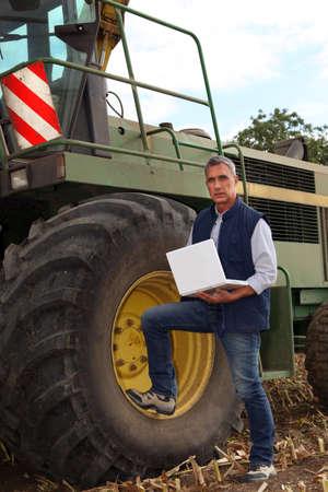 combine harvester: un agricultor y su computadora port�til cerca de una cosechadora