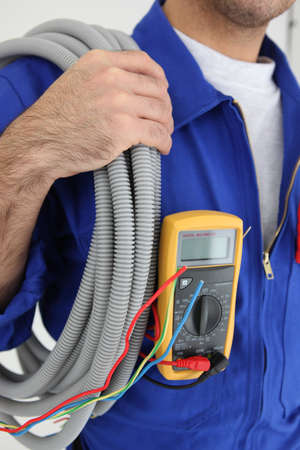 charged: Cropped shot of an electrician with a roll of cable and a voltmeter in his pocket