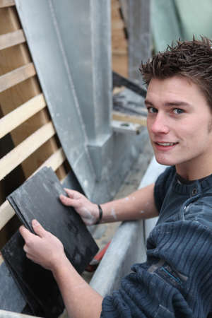 Young man with bitumen roof tiles photo