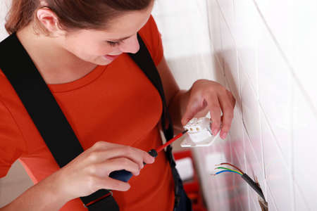 against the current: Woman screwing plug Stock Photo