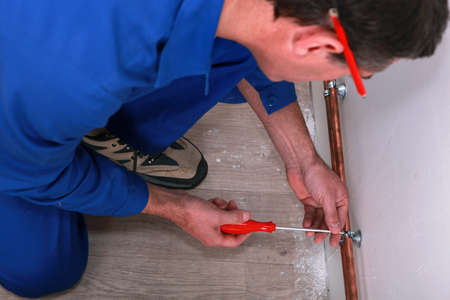 Plumber screwing a copper pipe to the wall Stock Photo