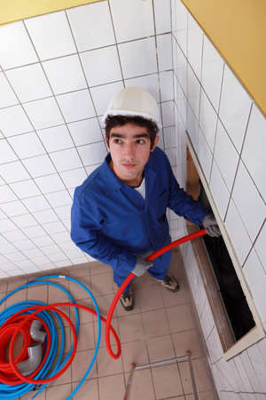 flexi: Young man feeding red flexible piping through a large hole in the wall Stock Photo