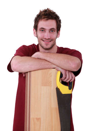 tongue and groove: Handsome young man with a floorboard and saw