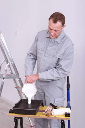 decorator: Decorator pouring paint into a tray Stock Photo