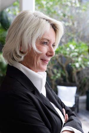 senior adult woman: senior businesswoman looking through the window