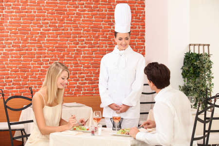 Chef talking to a couple in a restaurant photo