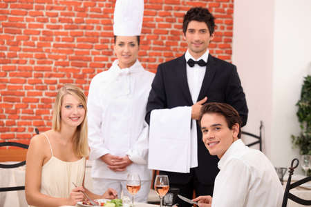 Restaurant staff stood with customers photo