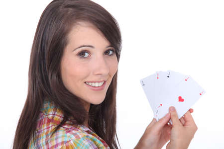 bluff: Young brunette with poker cards Stock Photo