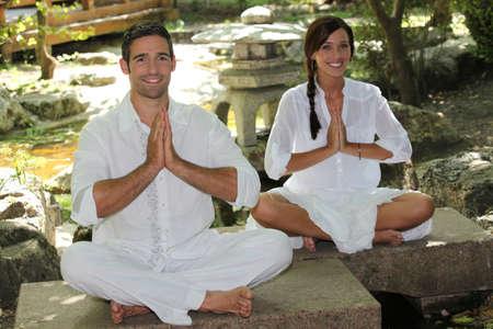 sat: Man and woman sat in garden meditating Stock Photo