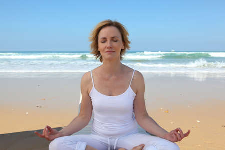 Woman meditating on the beach photo