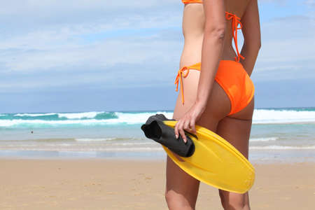 two piece: Woman in a bright orange bikini on the beach with a pair of flippers Stock Photo
