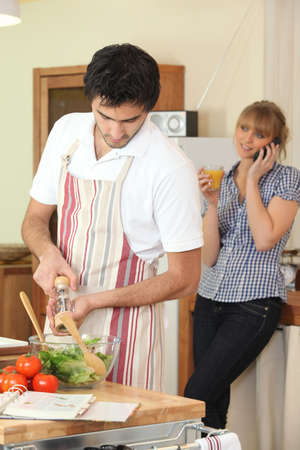 Husband cooking whilst wife telephones