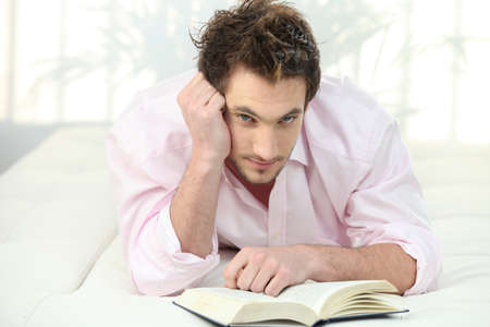 Man reading a book in bed Stock Photo - 22256215