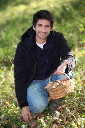 young man gathering mushrooms Stock Photo - 22256369