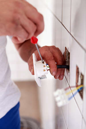 Electrician wiring a wall socket photo
