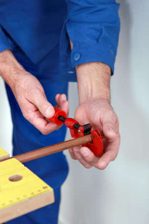 knurled: Plumber with a pipe cutter Stock Photo