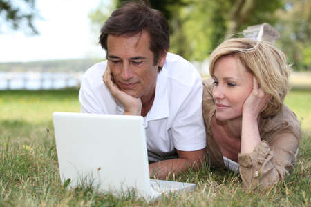 Couple lying in the grass looking at a laptop