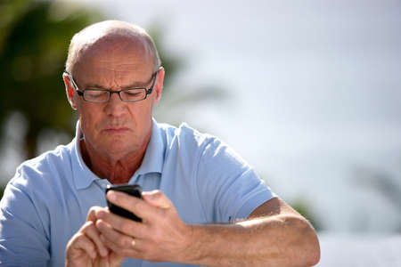Senior man sending text message photo