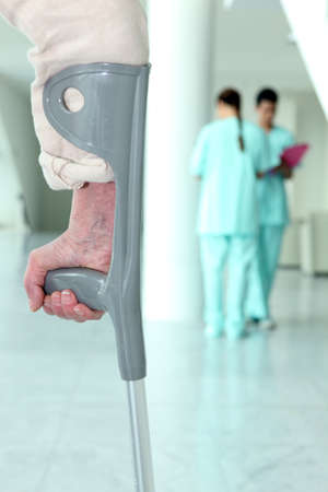 crutch: senior patient walking with a crutch in the hospital Stock Photo